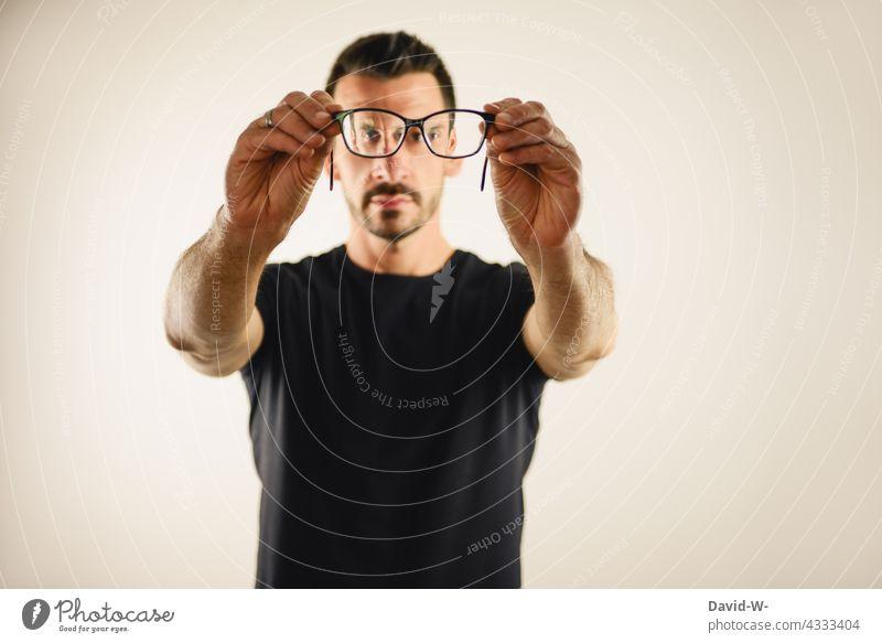 genau hinschauen - Mann schaut durch eine Brille Durchblick beobachten suchen Augen Sehvermögen Brillenträger Optik Brillenglasstärke blind
