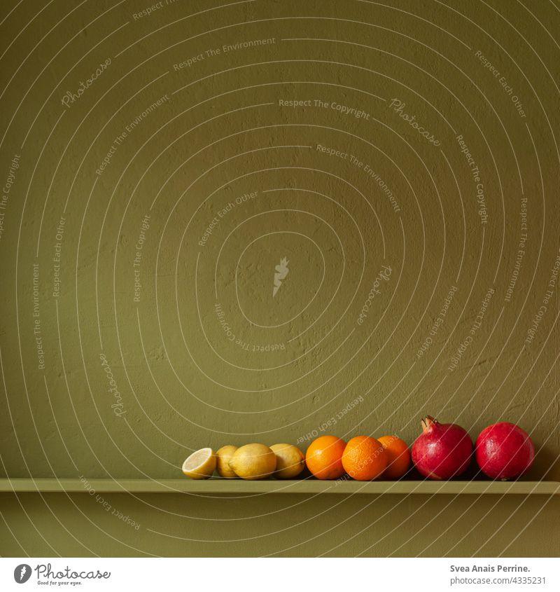 Obst vor grüner Wand Zitrone orange Granatapfel Gesundheit Gesunde Ernährung gelb orange-rot Stillleben Vegane Ernährung Farbkontrast Essen Essen zubereiten