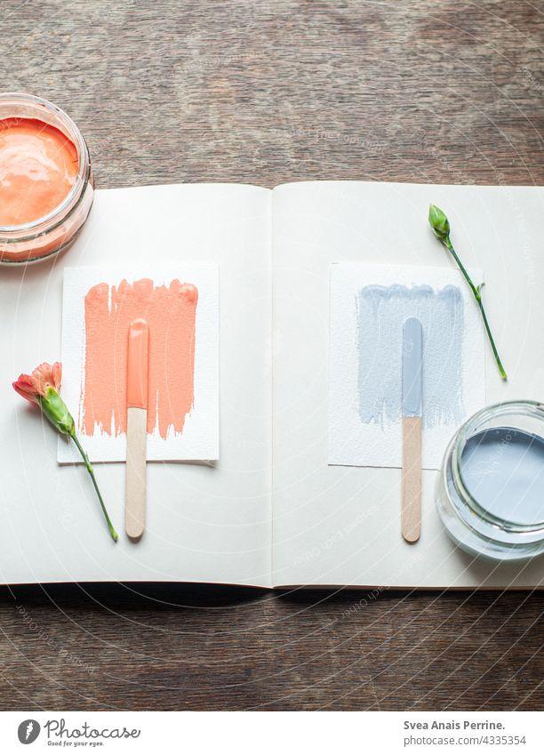 orange & hellblau Farbe wandfarbe malen hell-blau Holz Holztisch Blumen flatlay farbdesign Buch Kreativität Inspiration Holzstab Vogelperspektive Stillleben