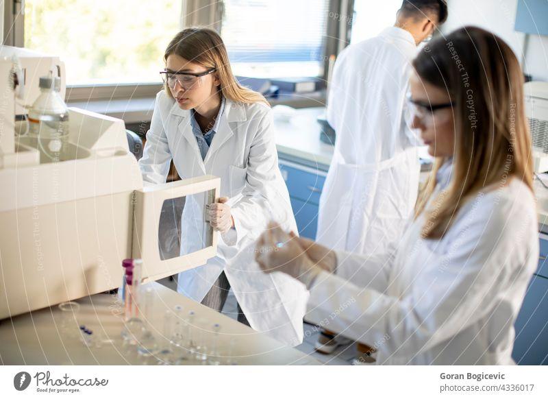 Weibliche Wissenschaftler in einem weißen Laborkittel setzen Fläschchen mit einer Probe für eine Analyse auf einem Ionenchromatographie-System im biomedizinischen Labor