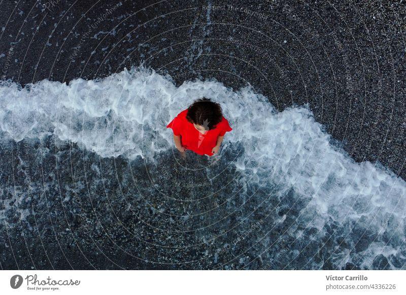 Draufsicht auf eine Frau in einem roten Kleid mit Meerschaum-Hintergrund Wasser MEER winken Strand blau Natur Wellen Sommer platschen Spray schäumen Küste