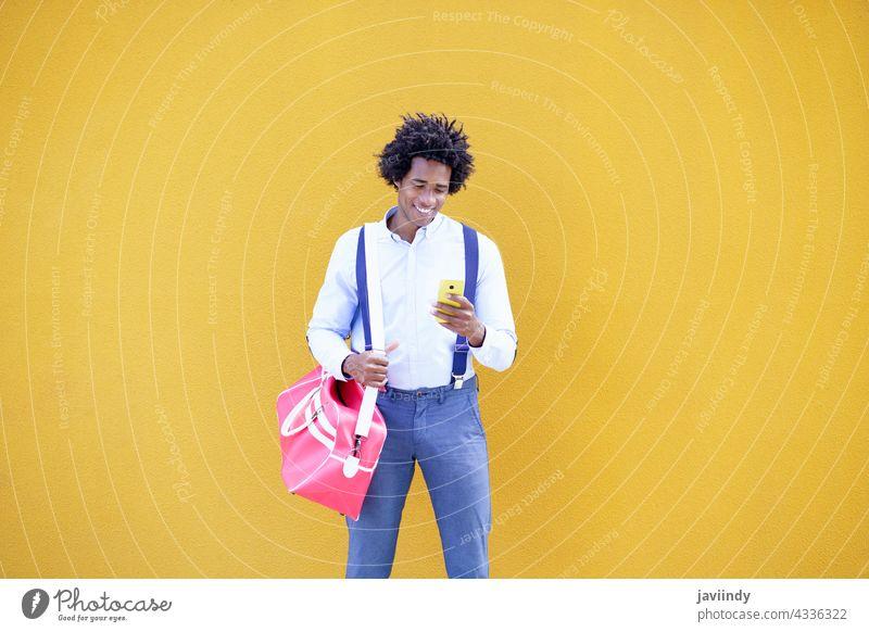 Schwarzer Mann mit Afro-Frisur trägt eine Sporttasche und Smartphone in gelbem Hintergrund. Geschäftsmann schwarz Tasche Business Afro-Look lockig Behaarung Typ