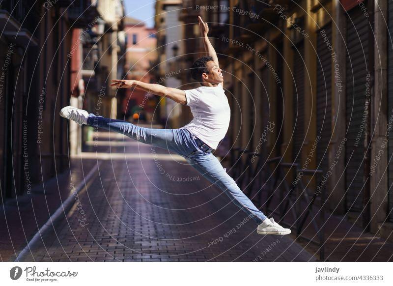 Schwarzer athletischer Mann macht einen akrobatischen Sprung im Freien schwarz Straße springen männlich Kubaner springend jung Fröhlichkeit Person Glück lässig