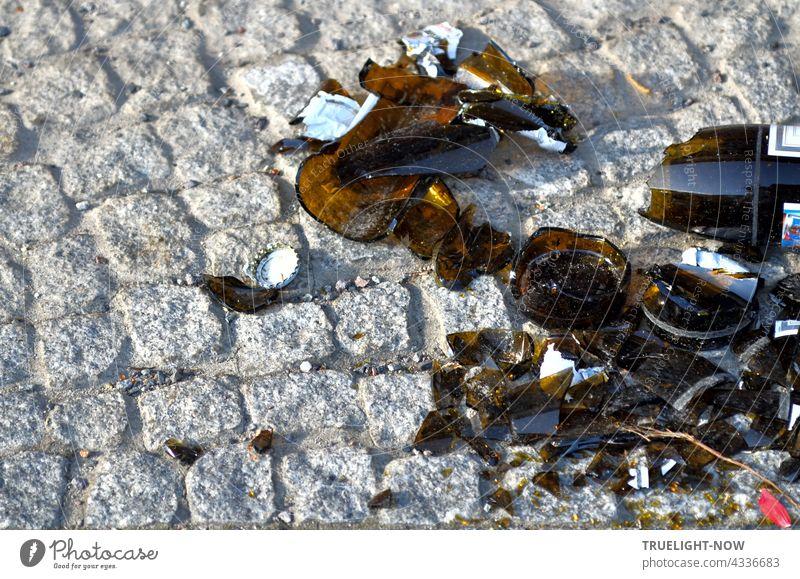Auf schön gesetzten grauen Pflastersteinen bilden die achtlos liegengelassenen Scherben einer in tausend Stücke zersprungenen braunen Flasche mit Kronkorken einen pittoresk hässlichen Kontrast