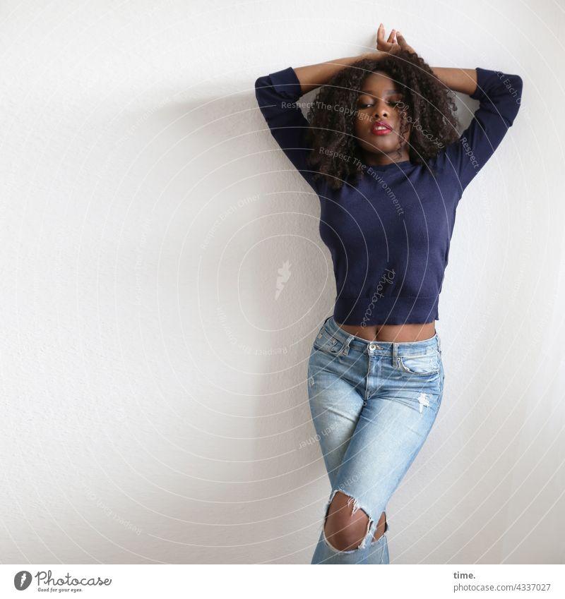 Arabella Vorderansicht Porträt Konzentration Inspiration erleben Willensstärke selbstbewußt schön warten stehen Blick Locken langhaarig Pullover Jeanshose Frau