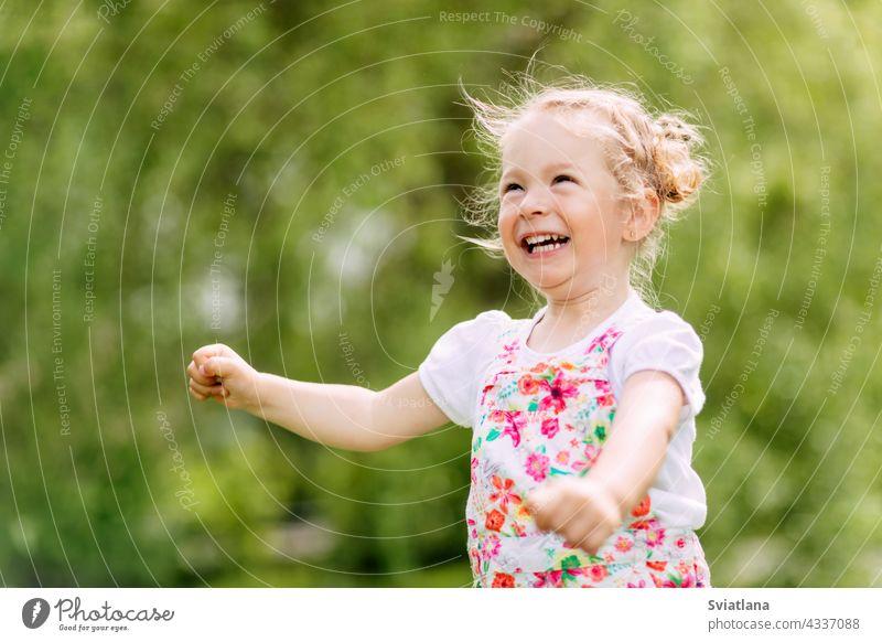 Glückliches lachendes Baby-Mädchen, das in einem Kleefeld läuftEin glückliches lachendes Baby läuft durch den Park oder Garten. Sommer, Sommerzeit, glückliche Tage