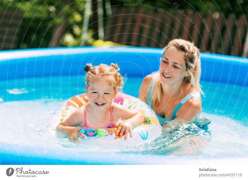Eine junge Mutter bringt ihrer kleinen Tochter mit Hilfe eines aufblasbaren Kreises das Schwimmen im Pool im Garten bei Mama Badeanzug aufblasbarer Kreis Wasser