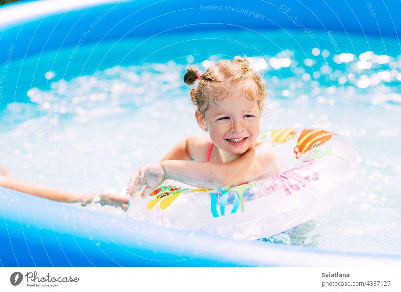 Ein lachendes Baby im hellen Badeanzug lernt mit Hilfe eines aufblasbaren Kreises das Schwimmen im Pool im Garten. Sommerzeit, Erholung, Rückansicht Mädchen