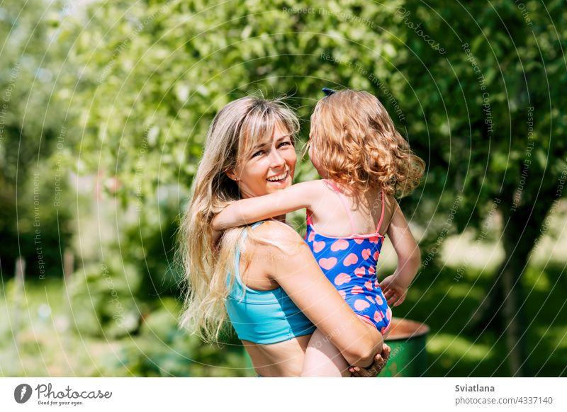 Eine junge Mutter hält ihre kleine Tochter in den Armen an einem Sommertag im Garten oder Park wenig Familie Eltern Mama Kind Kindheit Glück