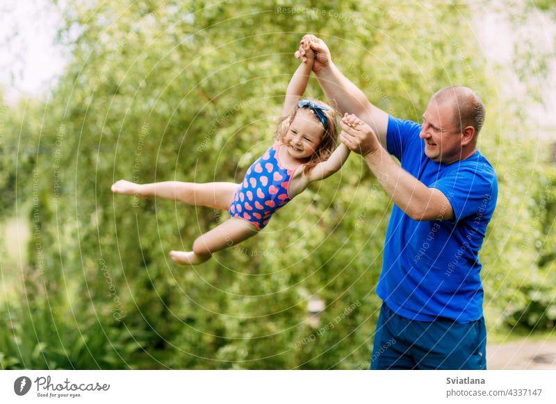 Ein niedlicher Vater und ein kleines Mädchen spielen zusammen. Das Kind nimmt in den Händen seines Vaters ab Baby Zusammensein fliegen Spielen Tochter Mann Park