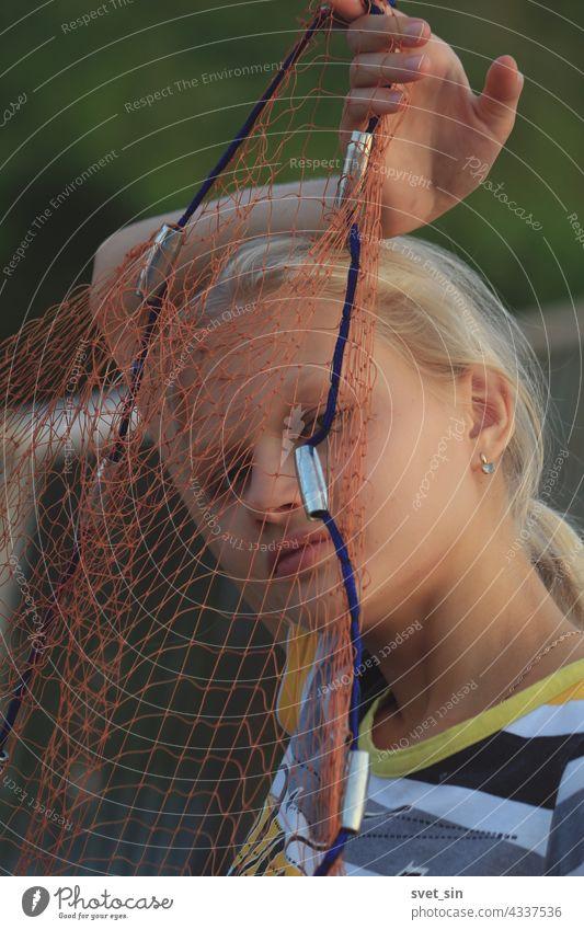 Porträt eines blonden Teenager-Mädchens durch ein Fischernetz. Ein blondes Mädchen hält ein Angelgerät vor ihrem Gesicht im Freien. Netzstrümpfe Natur Brücke