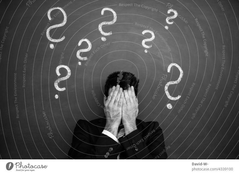 Fragezeichen über einem Kopf eines verzweifelten Mannes Ängste Zukunftsangst ? Problematik Sorge konzept Konzeptfotografie Irritation Verwirrung