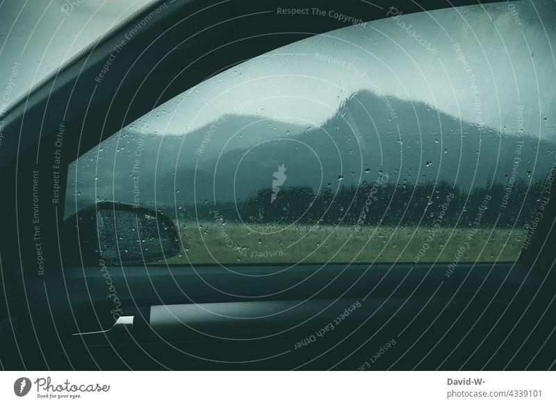 Im sicheren Auto während es draußen gewittert Gewitter Regentropfen Fensterscheibe Unwetter trocken nass Sicherheit schlechtes Wetter Klimawandel Urlaub Berge
