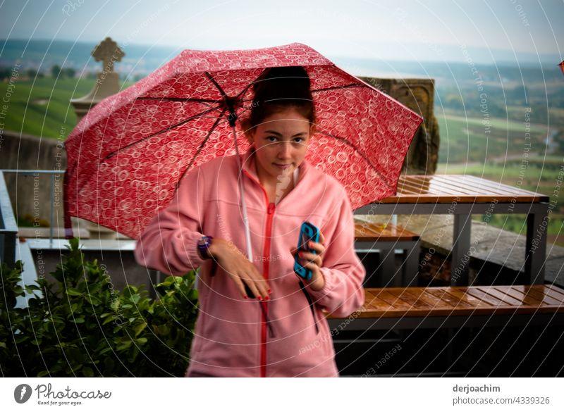 Alles in Rosa. Junges Girl steht mit Schirm und Regenjacke im Außenbereich des  Restaurant.  Das Handy in der Hand und schaut verzweifelt zu dem Fotografen,  wann ist  er endlich fertig .