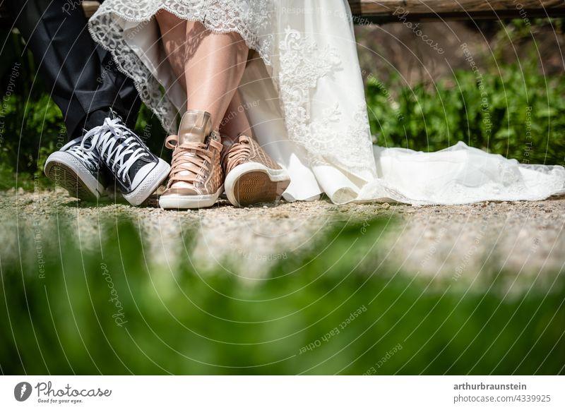 Junges Hochzeitspaar in Sneaker Schuhen sitzt auf einer Bank in der Natur hochzeit Liebe Paar Außenaufnahme Liebespaar Partnerschaft Ehe 2 Zusammensein Frau