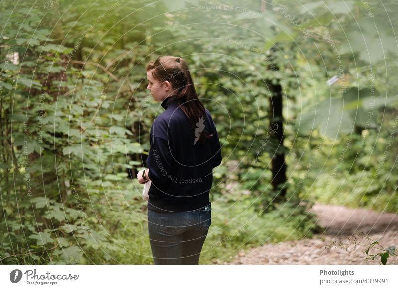 Junge Frau geht durch den Wald und beobachtet etwas. Natur natürlich grün Außenaufnahme Baum beobachtend wandern Person Textfreiraum Bäume Weg Pferdeschwanz