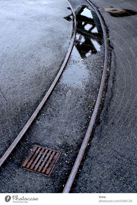 Gleis im Asphalt mit Abfluss, Pfütze und Spiegelung Schienenweg Gully Gullydeckel spiegelung grau nass feucht wasser schwingung krümmung parallel