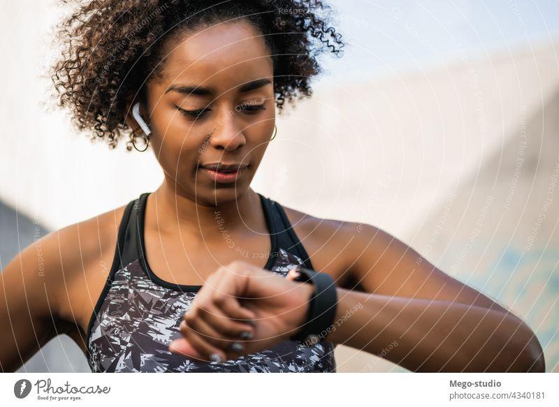 Fitness-Frau, die die Zeit auf einer Smartwatch überprüft. Afro-Look Übung Überprüfung smartwatch trainiert. Sport Sportler Gerät aktiv Körper Motivation Herz