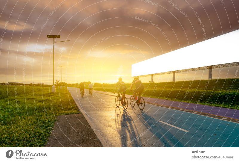 Sport Mann reiten Fahrräder auf der Straße am Abend in der Nähe von leeren Werbung Plakatwand mit Sonnenuntergang Himmel. Sommer im Freien Übung für gesunde und glückliche Leben. Radfahrer Reiten Mountainbike auf Radweg.