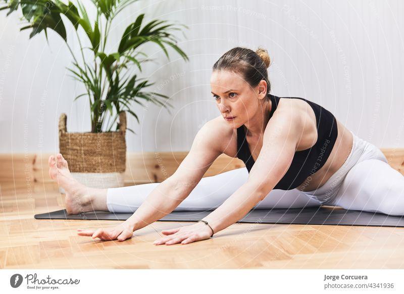 Teilausschnitt einer russischen Frau beim Üben von Yoga-Nudeln auf einer Matte Übung Pilates Körper Mädchen Training Behaarung praktizieren strecken Yogi jung