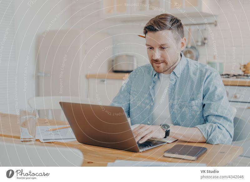 Fokussierte junge Mann Freiberufler mit Laptop, während am Küchentisch sitzen arbeiten aus der Ferne heimwärts Daten gutaussehend Lächeln im Innenbereich
