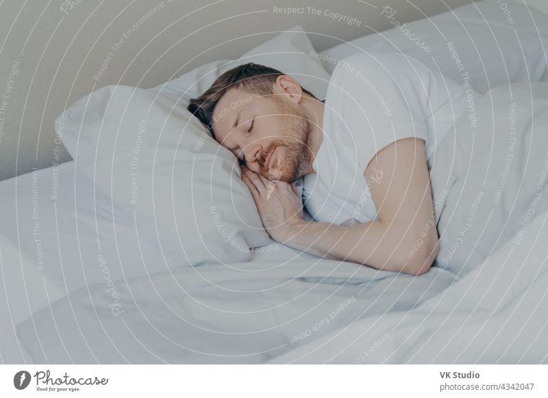 Hübscher junger Mann schläft bequem im Bett zu Hause schlafen Mittagsschlaf Glück gutaussehend Schlafzimmer gemütlich Streu sich[Akk] entspannen friedlich