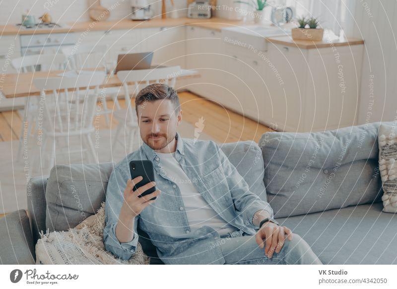 Attraktiver kaukasischer junger Mann in häuslicher Freizeitkleidung verwendet Smartphone zu Hause bärtig heiter Telefon Mobile Lächeln Sofa Person Positivität