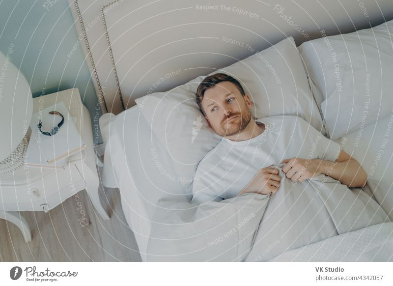 Handsome betont junge kaukasische männlich im Bett liegend mit seinen Augen offen Mann Lügen schlafen Stress Schlafzimmer Schlafstörung müde Raum rastlos