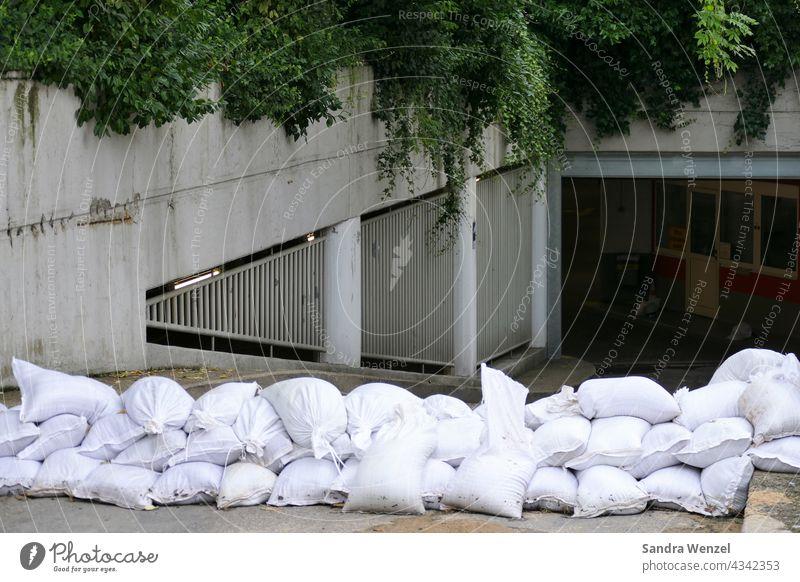 Sandsäcke vor einer Tiefgarage Hochwasser Sommer 2021 Starkregen Dauerregen Unwetter Flut Ufer überflutet Elementarschäden Gebäudeversicherung Schutzwand