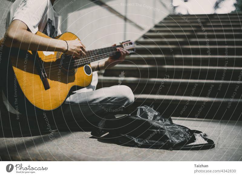 Straßenkünstler spielt Gitarre .  Junger Straßenmusiker spielt Gitarre und busking für Geld Künstler Musik Musical Musiker Künstlerin spielen Spieler Klang