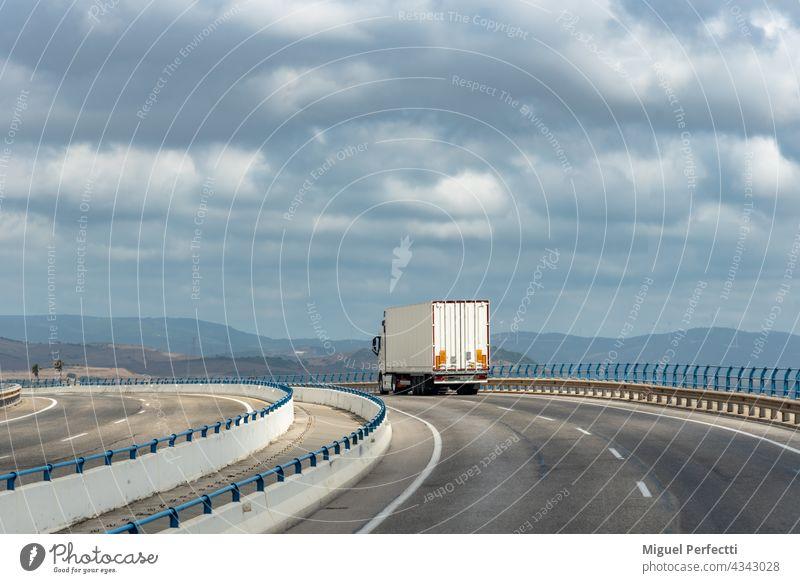 LKW mit Metallsattelauflieger, weit verbreitet in der Textil- und Automobilindustrie, fährt über eine Brücke mit bewölktem Himmel. Lastwagen Anhänger Straße
