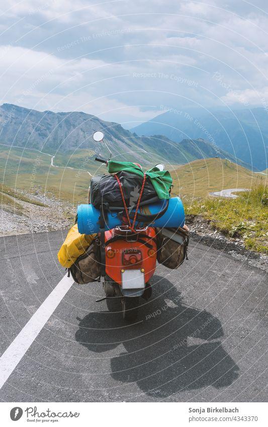 Überladener nostalgischer Motorroller parkt in den Hochalpen (Großglockner Hochalpenstraße), Österreich, im Sommer motorroller oldtimer beladen überladen gepäck