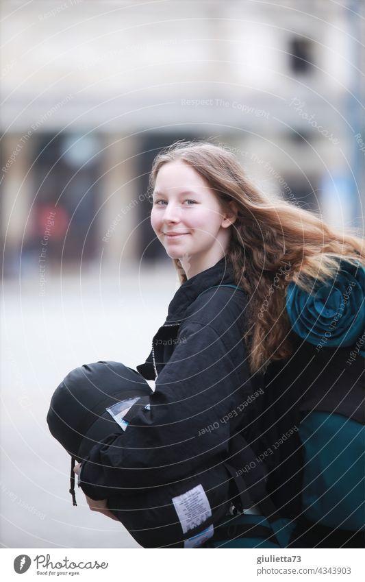 Ab in die Ferien! Teenager Mädchen mit Rucksack und Schlafsack bereit für den Camping-Urlaub Porträt jung hübsch Glück Wandel & Veränderung Gedeckte Farben
