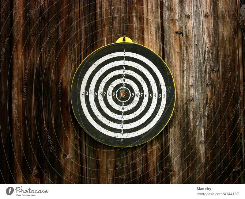 Alte runde Zielscheibe für das Dartspiel mit Pfeilen auf dem braunen Holz einer alten Scheune in Rudersau bei Rottenbuch im Kreis Weilheim-Schongau in Oberbayern