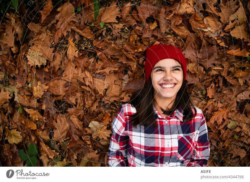 Lachen Teenager-Mädchen liegt in einem Bett von trockenen Blättern im Herbst Glück Lächeln Lügen Freude Spaß positiv heiter Textfreiraum trocknen Auge