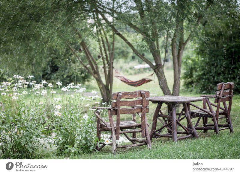 wohlfühlzone. sitzgruppe Holztisch Holzstuhl holzmöbel Natur Blumen Hängematte ausruhen chillen Teichufer Bäume Sommer Außenaufnahme Pause Sitzgelegenheit