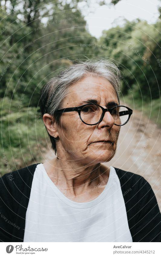 Nachdenkliche ernste ängstliche reife ältere Frau, nachdenkliche traurige Dame, die wegschaut und an Einsamkeit, Älterwerden und Depression denkt Person