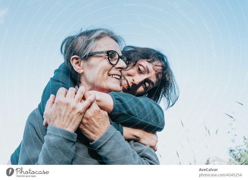 Senior Frau und ihre Tochter lächelnd und mit Spaß auf der Natur während eines sonnigen Tages. Glücklich Muttertag Freude Lachen Zusammengehörigkeitsgefühl