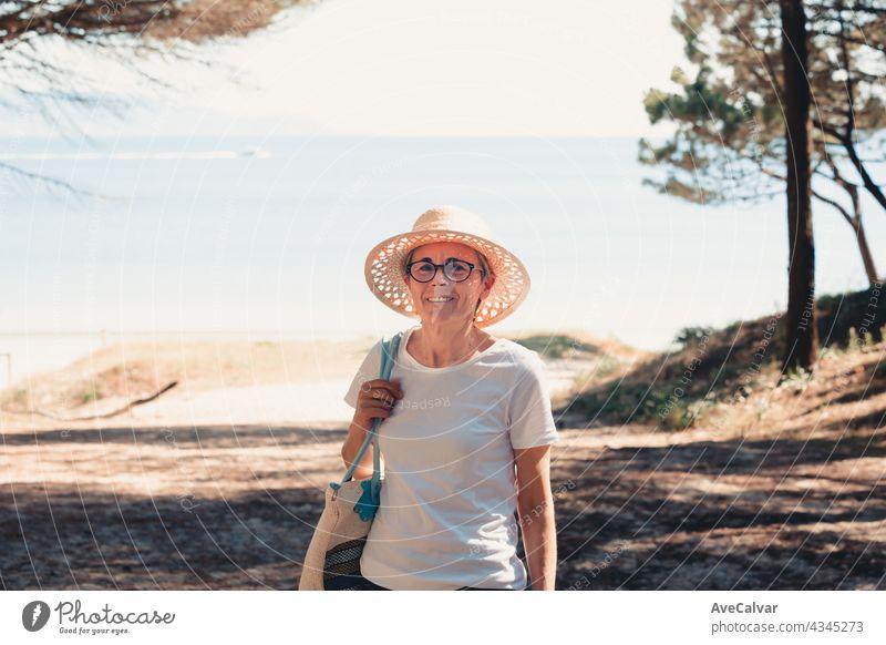 oman mit grauen Haaren am Strand während einer super sonnigen Tag, Senior Freiheit Konzept, Kopie Raum, entspannen und geistige Gesundheit Person Frau älter