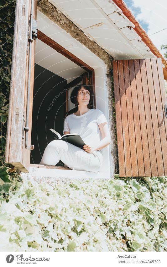 Eine junge Frau mit einem Buch sitzt auf der Fensterbank, Lesen und Entspannen während eines sonnigen Tages Teenager Person Bildung im Innenbereich lesen Raum