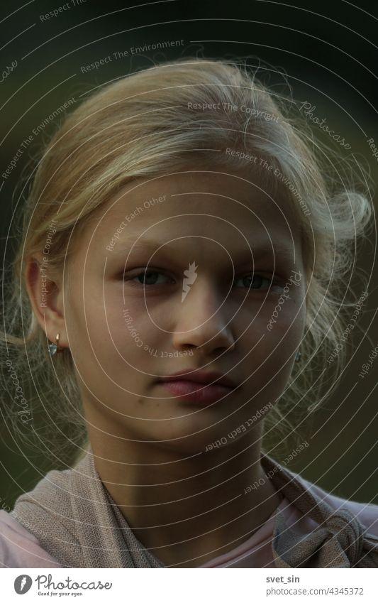 Porträt eines blonden Mädchens im Abendlicht im Freien. Gesicht Teenager Sommer in die Kamera schauen natürlich träumend ländlich allein Jugend Glück posierend