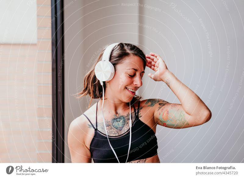 glückliche muskulöse kaukasische Frau, die Musik auf dem Handy und Headset in der Turnhalle hört. Tanzen am Fenster während der Tageszeit. Sport und gesunder Lebensstil