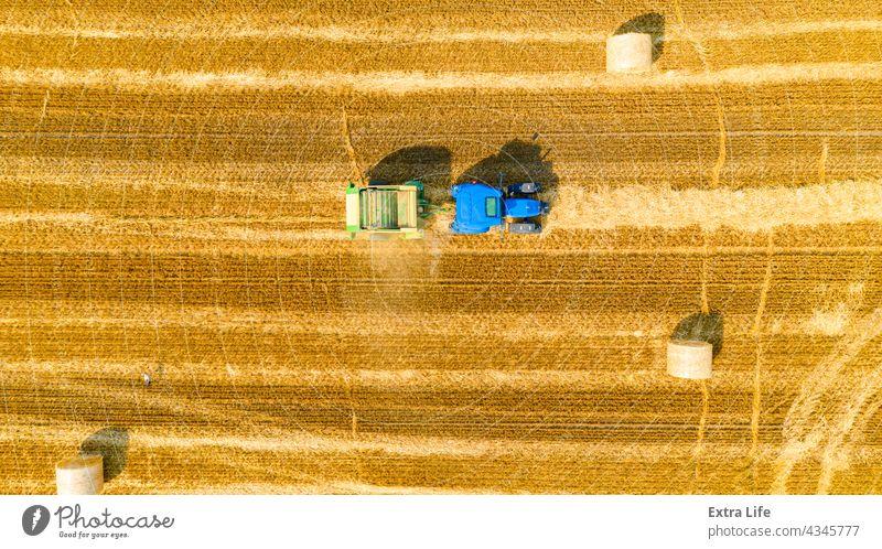 Luftaufnahme einer vom Traktor gezogenen Ballenmaschine zum Einsammeln von Stroh vom abgeernteten Feld oben Antenne landwirtschaftlich Ackerbau anbaufähig