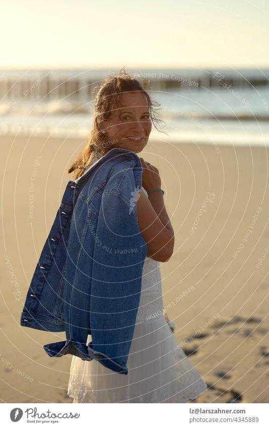 Attraktive Frau mittleren Alters in einem eleganten weißen Kleid, die einen Blumenstrauß und eine Jacke über der Schulter trägt und über einen verlassenen Strand bei Sonnenuntergang läuft, wobei sie sich umdreht und in die Kamera lächelt