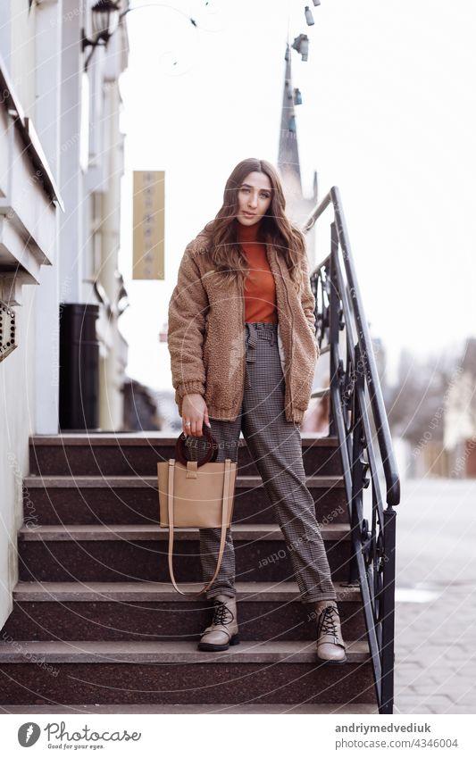Mode-Stil Porträt. schöne stilvolle Mädchen mit langen Haaren Spaziergänge in der Stadt. Porträt von attraktiven Mädchen auf der Straße. Frühling oder Herbst Tag. selektiven Fokus.