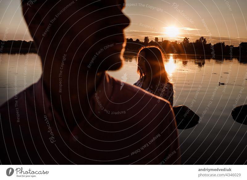Silhouette von Paar in der Liebe in der Nähe des Sees auf Sonnenuntergang. Lovely glückliches Paar, das Spaß in der Nähe im Freien. glücklichen Urlaub Konzept. selektiven Fokus