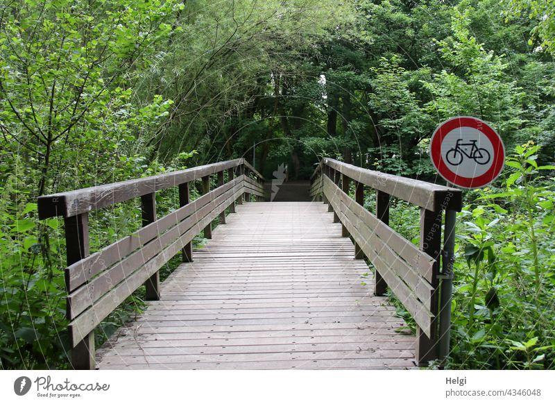 Keine Fahrräder! - Holzbrücke im Park mit Verbotsschild für Radfahrer Brücke Verkehrsschild Verbot für Radfahrer Baum Strauch Fußweg Geländer