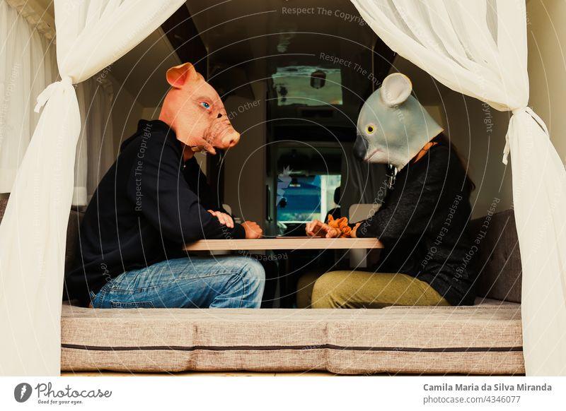 Ehepaar mit Tieren am Tisch sitzend in einem Wohnmobil. Reisendes Paar. Abenteuer Tiere Maske Auto nach Hause PKW fahren Freiheit Glück Feiertag heimwärts Koala