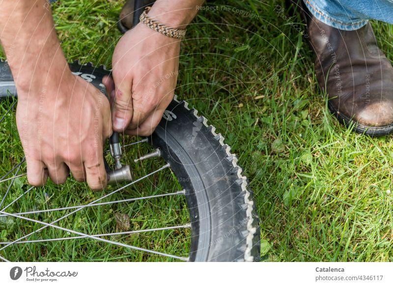 Hände setzen Luftpumpe aufs Ventil eines Fahrradreifens Handarbeit Aufpumpen Speichen Felge Stiefel Jeans Gras Pflanze Tag tageslicht Nahaufnahme Grün