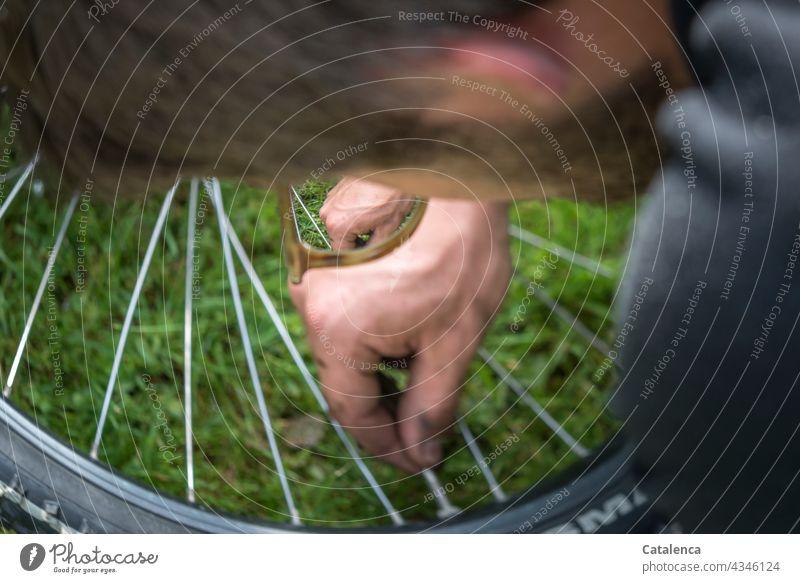 Junger mann überprüft das Ventil seines Fahrradreifens Hände Handarbeit Luftpumpe Aufpumpen Speichen Felge Stiefel Jeans Gras Pflanze Tag tageslicht Nahaufnahme